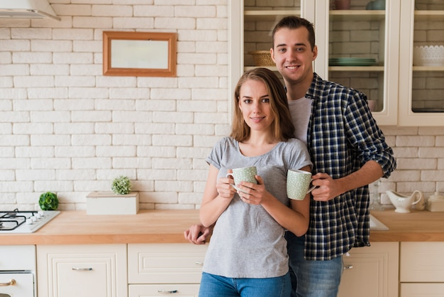 Tender bonding couple drinking brew and standing in kitchen Free Photo