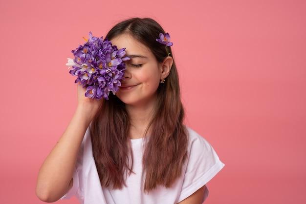 고립 된 보라색 봄 꽃과 흰색 티셔츠 Coned-one 눈에 부드러운 갈색 머리 소녀 프리미엄 사진