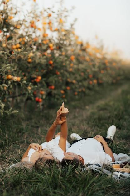 Нежная пара, лежа на зеленой траве и взявшись за руки. молодая пара устраивает пикник в яблоневом саду. Premium Фотографии