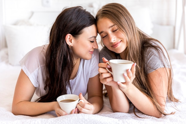 Tender couple with coffee on the bed Free Photo