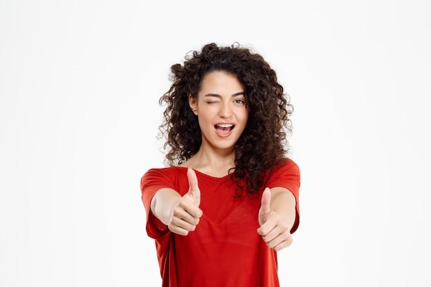優しい巻き毛の女の子笑顔と白い壁にokサインを指す 無料写真