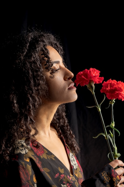 Tender ethnic woman with flowers in darkness Free Photo
