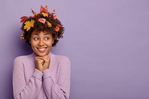 Tenera donna femminile tiene le mani sotto il mento, esprime emozioni positive dopo la passeggiata autunnale, ha il fogliame tra i capelli ricci vestito in maglione Foto Gratuite