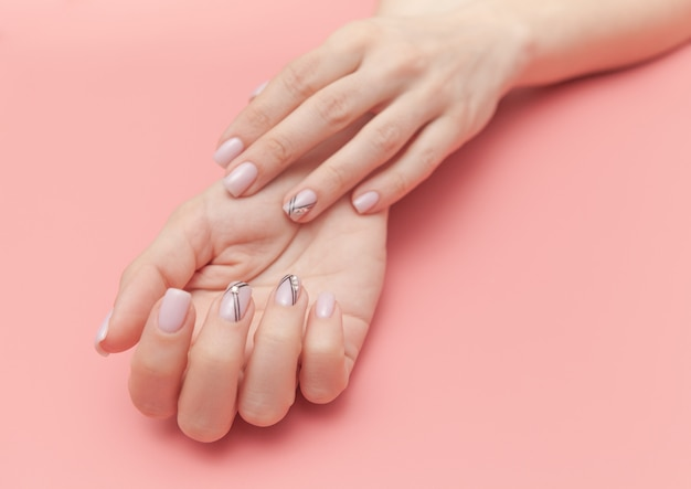 Tender hands with perfect nude manicure on pastel pink Premium Photo