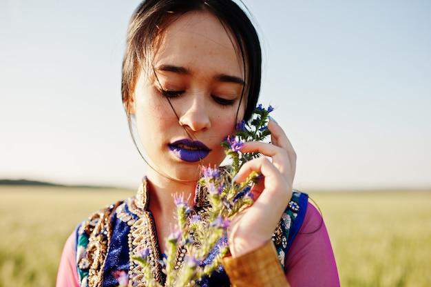 紫色の唇とサリーの柔らかいインドの女の子は、日没のフィールドでポーズを構成します。ファッショナブルなインドのモデル。 Premium写真