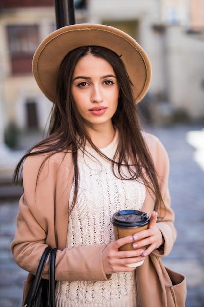 ハンドバッグと一杯のコーヒーを持って通りを歩く優しい女性。 無料写真