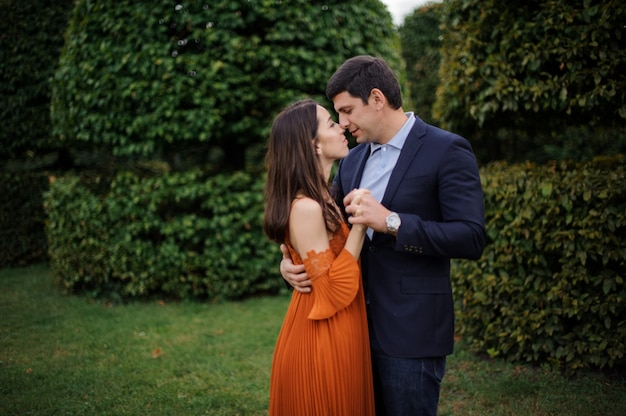 Tender love story of beautiful woman in orange dress and man in stylish suit Premium Photo