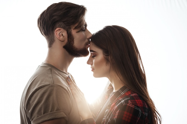Tender picture of young couple. man kissing woman to forehead. Free Photo