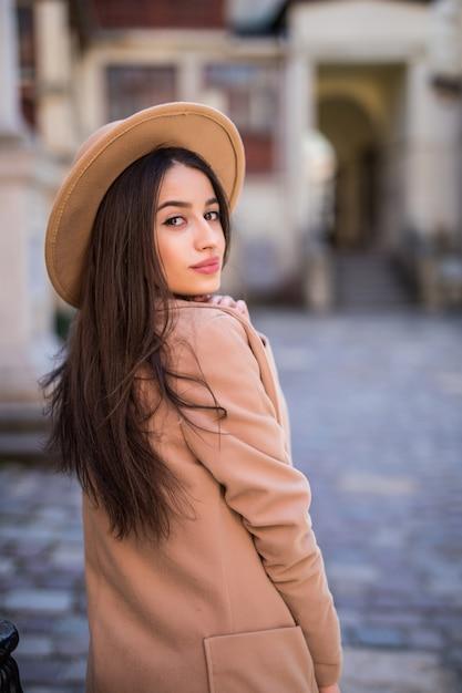 優しい笑顔の女性が通りを歩いているとカジュアルなモダンなコートと帽子でポーズ 無料写真