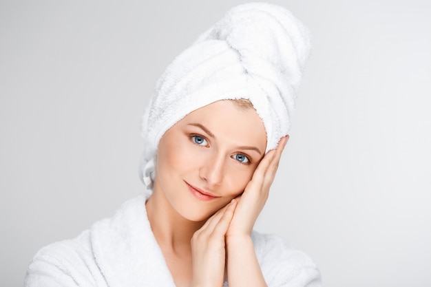 Tender smiling woman touching clean face Free Photo