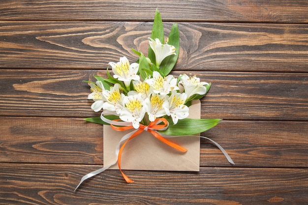 Tender white flowers small orchids in a crafty mail envelope on a wooden background Premium Photo