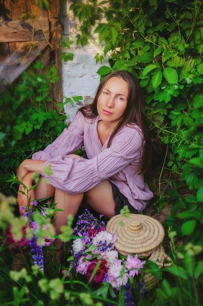 Нежная женщина отдыхает в травянистых зарослях с красивым букетом пионов и полевых цветов Premium Фотографии