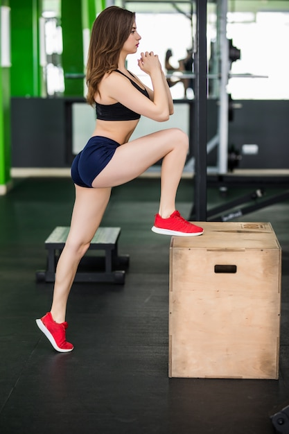 Tender woman with long hair is working with step box sport simulator in fitness gym Free Photo