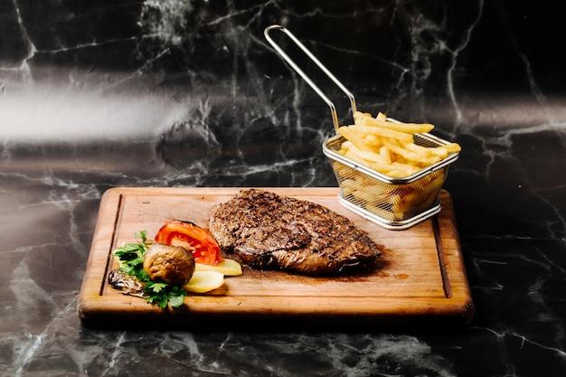 Tenderloin steak with grilled vegetables and french fries on a wooden board. Free Photo