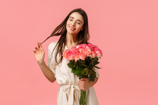 Tenderness, delight and valentines day concept. charming, lovely and sensual brunette woman in dress, rolling curl on hair happily close eyes and dreaming, receive flower delivery, hold roses Premium Photo