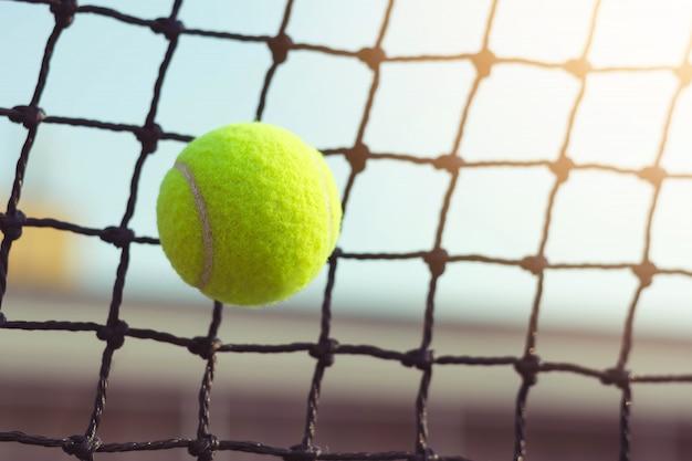 ぼかし裁判所の背景にネットに打つテニスボール Premium写真