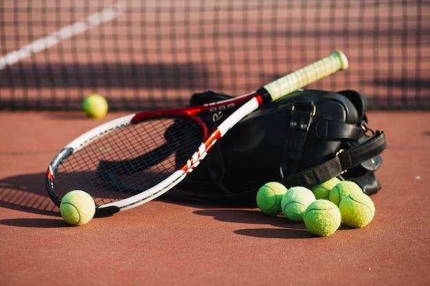 Теннисные мячи и ракетки на теннисном поле Premium Фотографии