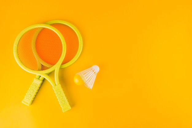 Tennis bats with shuttlecock and ball on yellow background Free Photo
