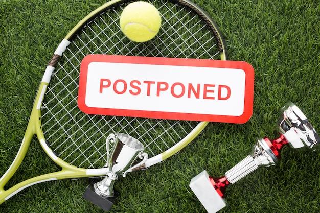 Tennis elements arrangement with postponed sign Free Photo