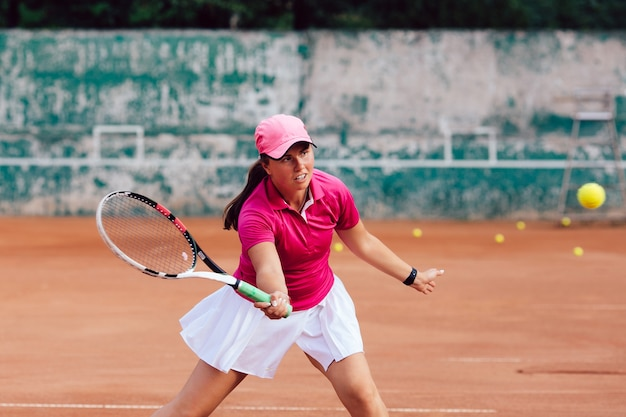 Tennis player. female player dressed in pink skirt and white blouse, playing tennis on court Free Photo