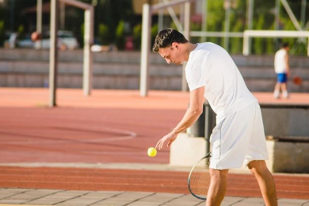 Tennis player preparing to serve Free Photo