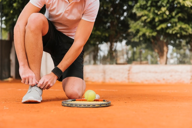Tennis player tying his shoelaces Free Photo