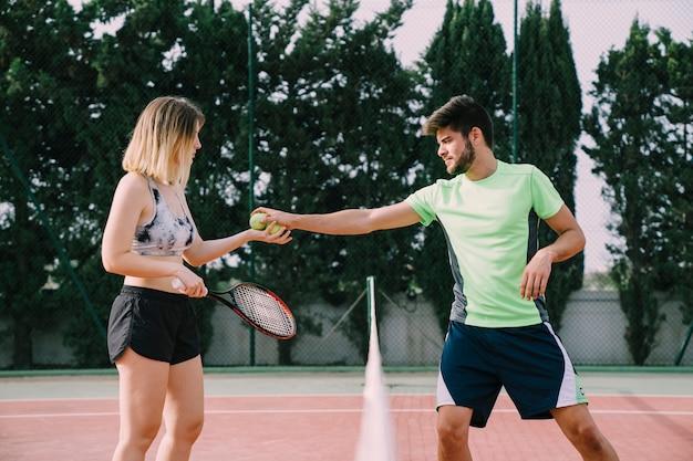 Tennis players interchanging ball Free Photo
