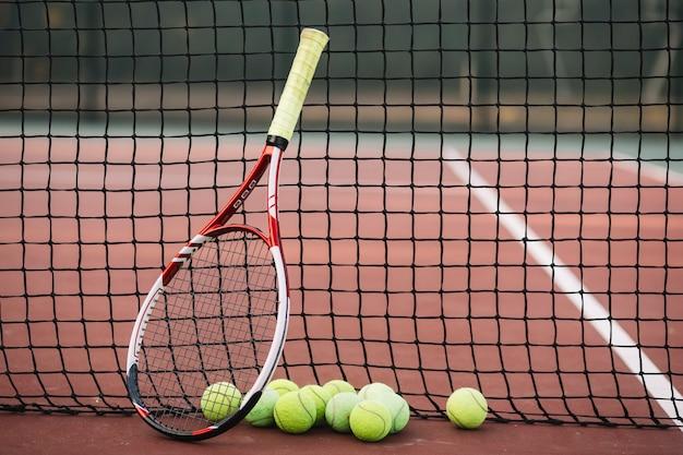Теннисная ракетка и мячи на теннисной сетке Premium Фотографии