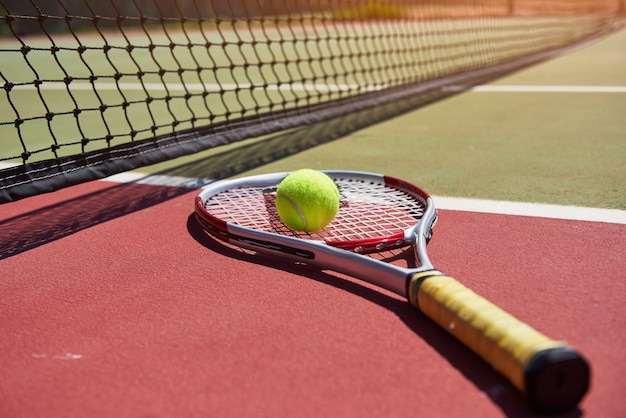 A tennis racket and new tennis ball on a freshly painted tennis court. Free Photo