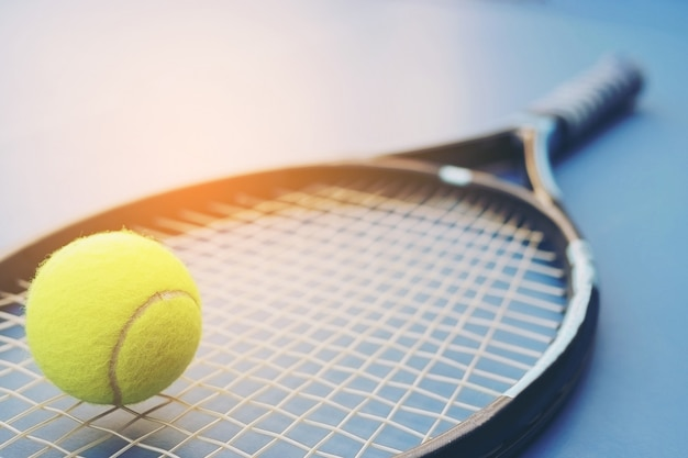 Tennis racket with ball on court Free Photo