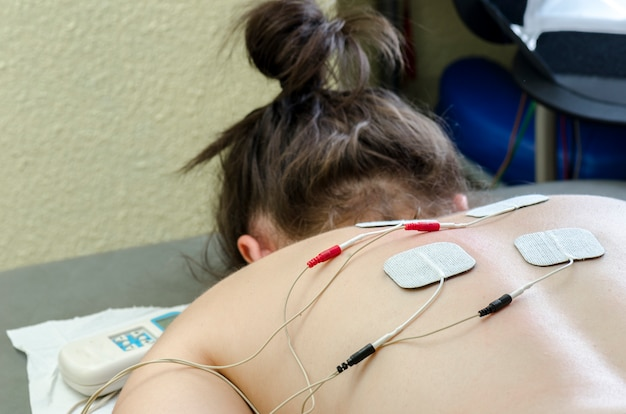 Tens electrodes positioned for back pain treatment in physical therapy Premium Photo
