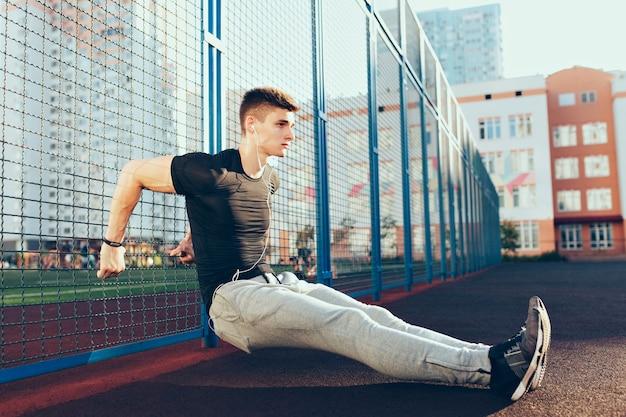 Напряженный парень с мускулистым телом на тренировке возле забора утром на стадионе. он носит спортивную одежду, слушает музыку в наушниках. он выглядит сосредоточенным. Бесплатные Фотографии
