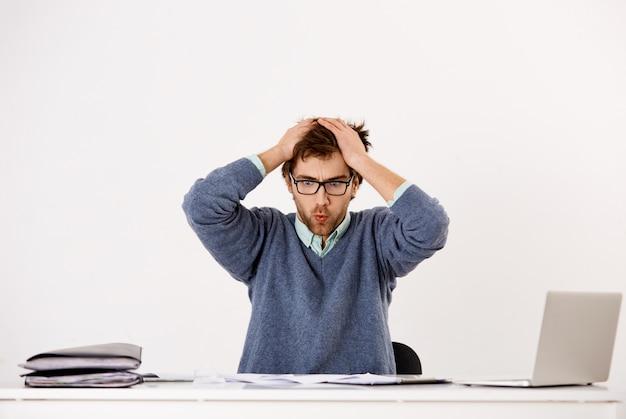 Напряженный и напряженный молодой работник мужского пола, офисный работник или предприниматель обеспокоен, выдыхая, как смотрит на документы и отчеты, не может справиться с давлением сроков Бесплатные Фотографии