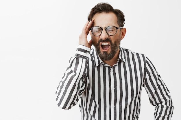 Напряженный и напряженный бородатый зрелый мужчина позирует Бесплатные Фотографии