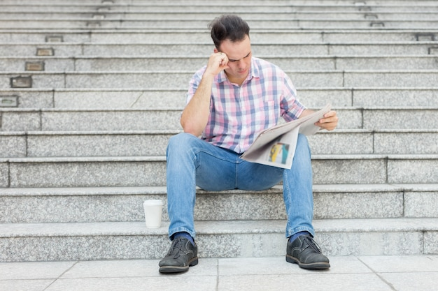 Tensed man reading newspaper on city stairway Free Photo