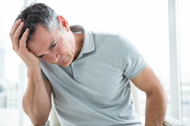 Tensed man sitting against window with his hand on head Premium Photo