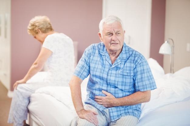 Tensed senior man and woman sitting on bed Premium Photo