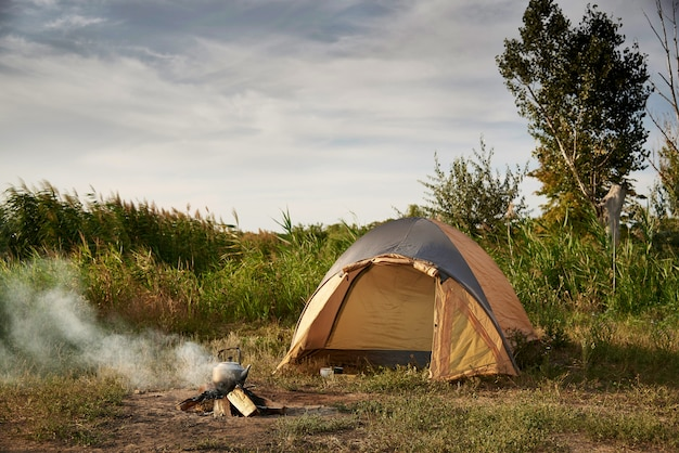 Tent on the shore of the lake near a burning fire with a kettle. Premium Photo