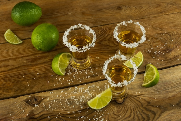 Tequila shots with lime and salt on the wooden surface top view Premium Photo