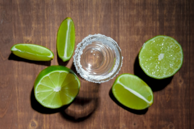 Tequila silver shots with lime slices and salt on wooden board Premium Photo