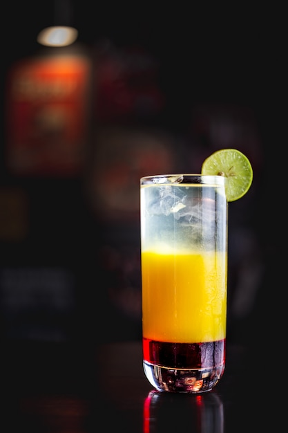 Tequila sunrise in a dark ambient bar Premium Photo