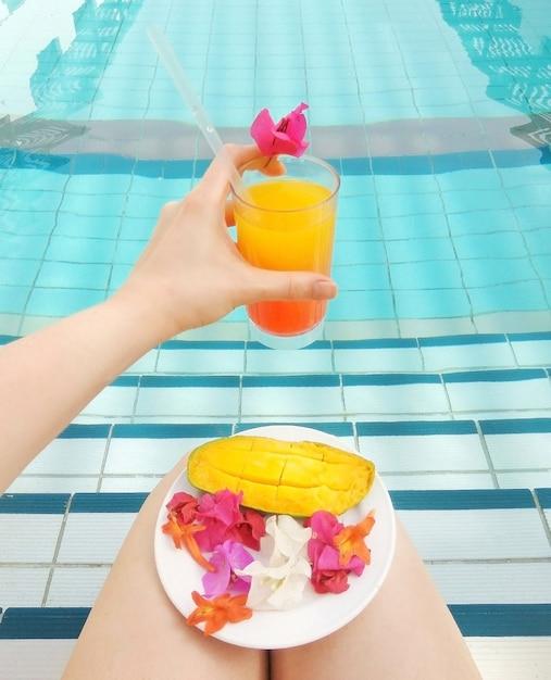 女性の手でテキーラの日の出またはオレンジジュースはプールでマンゴートロピカルフラワーブーゲンビリアを提供しました。ライフスタイルの職業リラックスレストスパ Premium写真