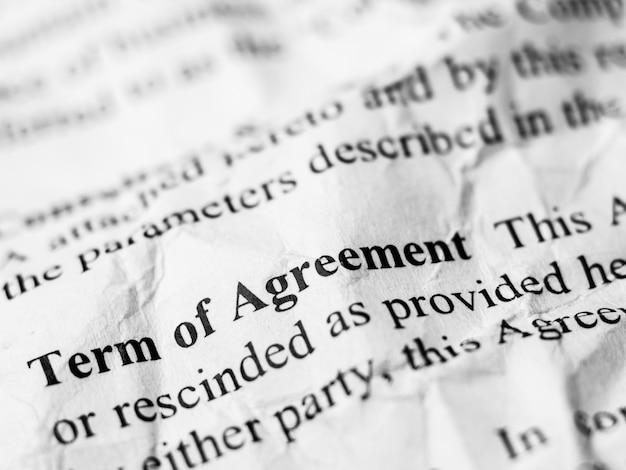 Срок действия слова «слово соглашения» на смятой и морщинистой бумаге Premium Фотографии