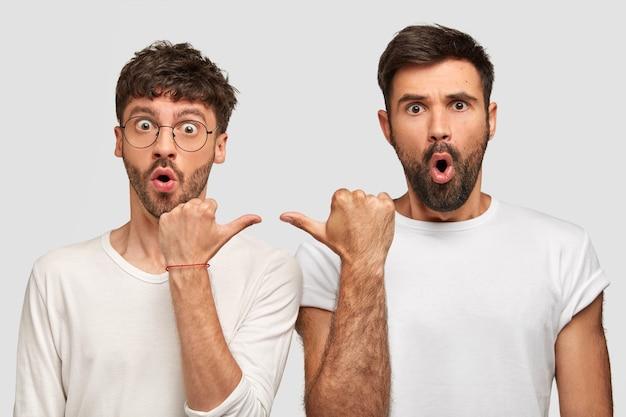 素晴らしいあごひげを生やした男たちは目を飛び出し、口を開けたまま、唖然とした表情でお互いを指さし、カジュアルな服を着て、白い壁に隔離されました 無料写真