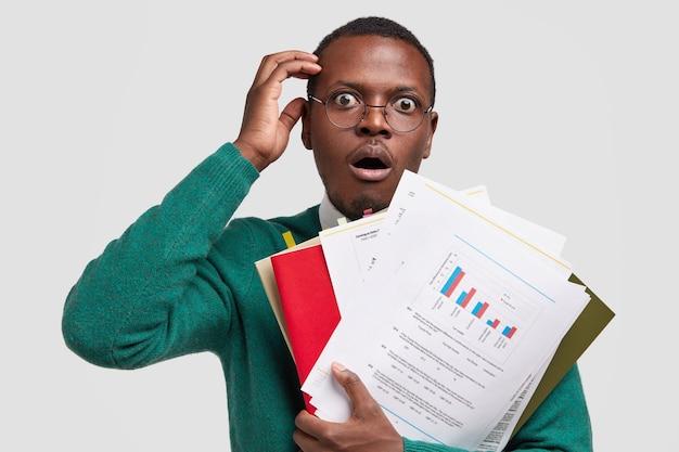 素晴らしい浅黒い肌の起業家は、会社の低所得に驚いたグラフィック図の紙を運び、財務計画をチェックし、眼鏡をかけます 無料写真