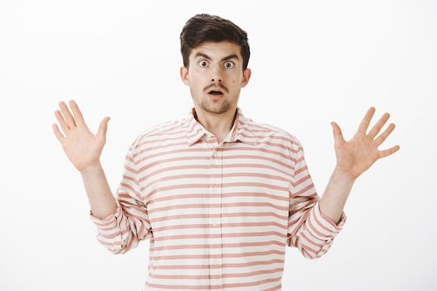 Terrified hostage afraid of being shot. portrait of intense shocked european man with beard, raising palms in surrender, popping eyes, being afraid and uncomfortable over gray wall Free Photo