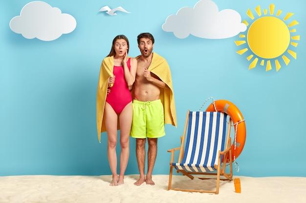 恐怖の恋人たちは近くに立ち、柔らかいタオルで覆われ、熱帯のビーチに立ち、目を大きく開いて見つめ、新婚旅行をします 無料写真