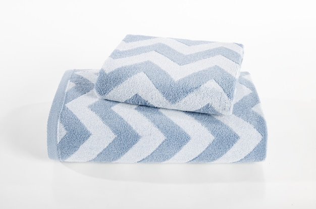 Terry towels stack, towels in stack against the white backdrop, stack of blue and white towels Premium Photo