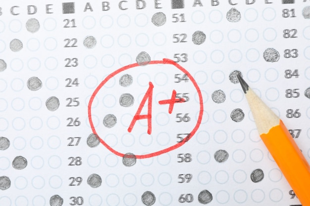 Test score sheet with answers, grade a+ and pencil, close up Premium Photo