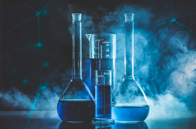Test tube and flask with blue liquid and blue smoke. chemistry and laboratory concept.